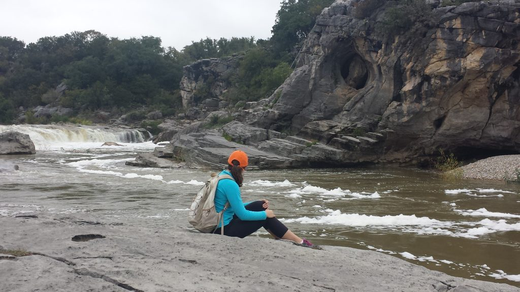 Kate Storm sitting on a rock overlooking Pedernales Falls on a cloudy day. Pedernales is one of the best places to camp near austin tx