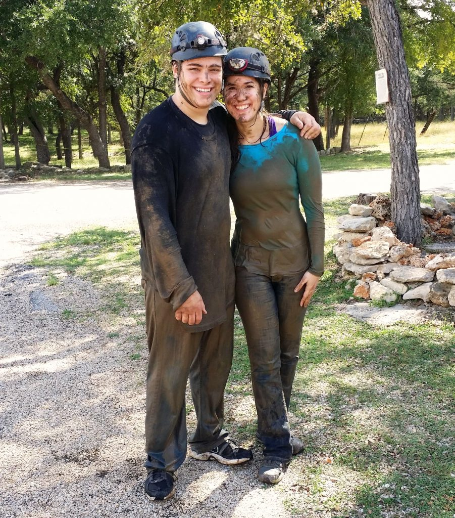 Kate Storm and Jeremy Storm wearing muddy clothes after an adventure tour in Cascade Caverns, one of the best caves in Texas