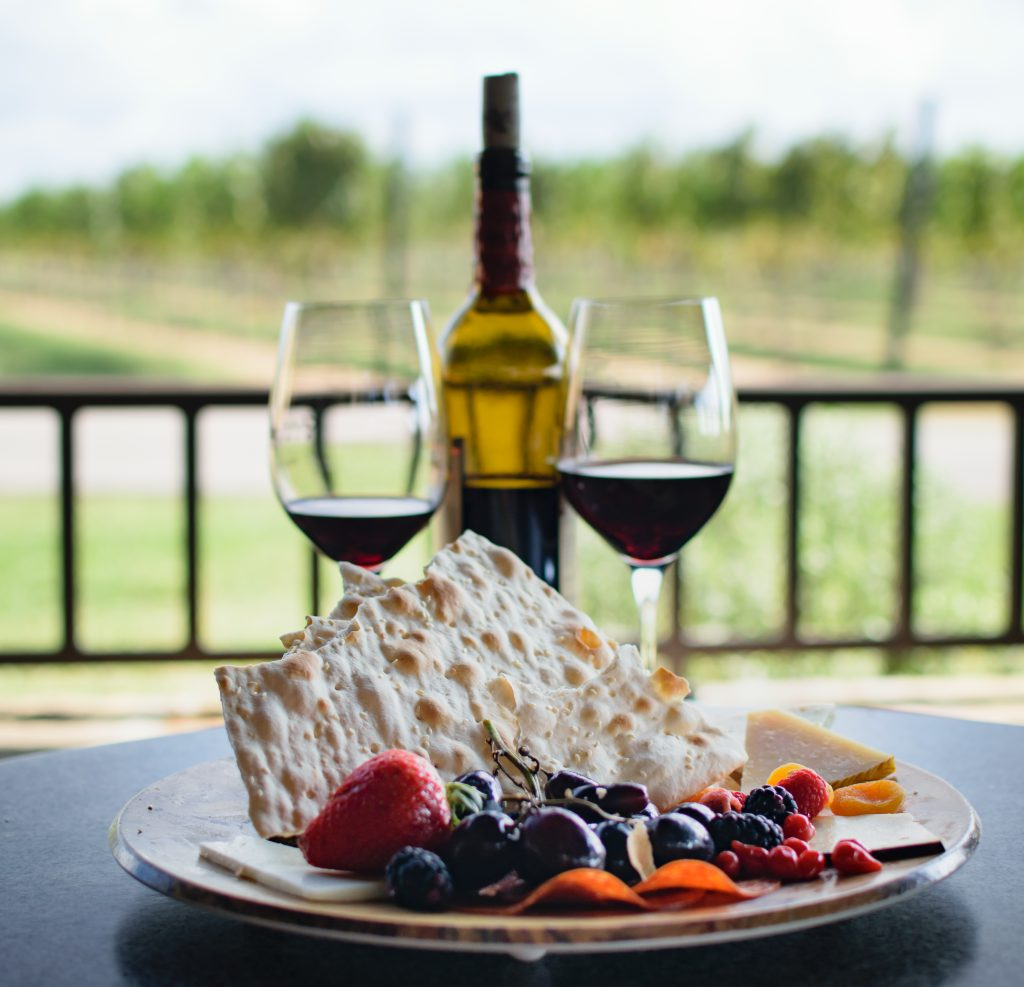 2 glasses of wine with a bottle between them and a plate of crackers and fruit in the foreground near Fredericksburg Texas
