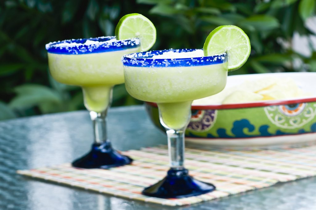 2 frozen margaritas in clear glasses with blue rims with lime slices on the side. Margaritas are one of the best things to drink to Texas!