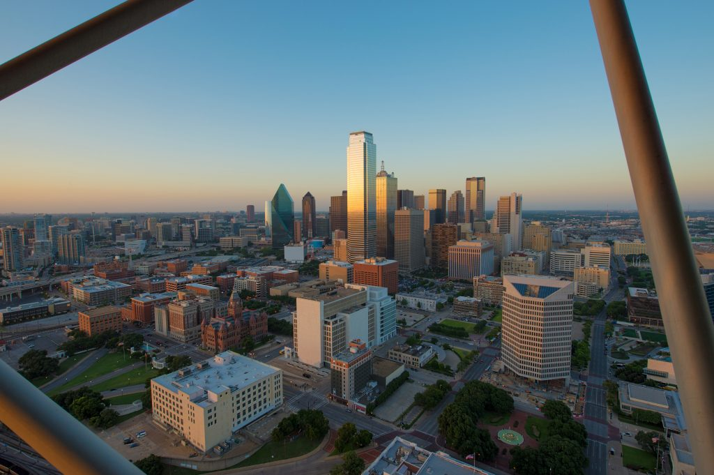 View of Dallas skyline from Reunion Tower with iron bars framing the skyline