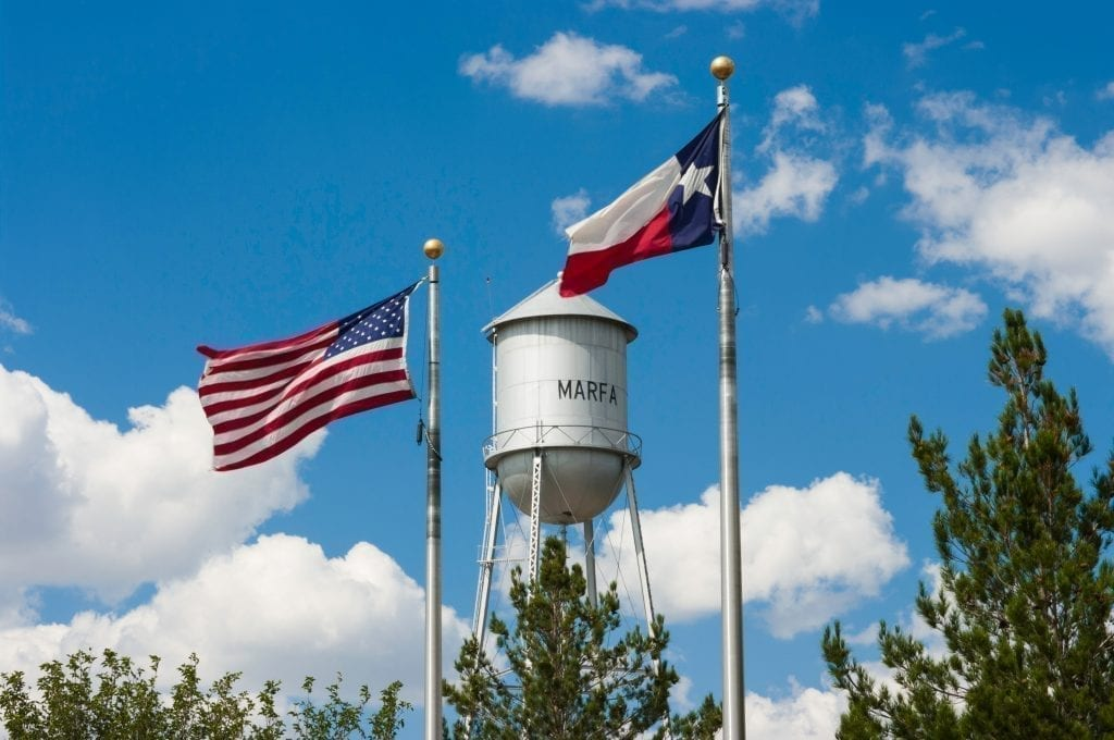 "Water town in Marfa Texas that says ""Marfa"" on the side with an American flag flying to its left and a Texas flag flying to its right"