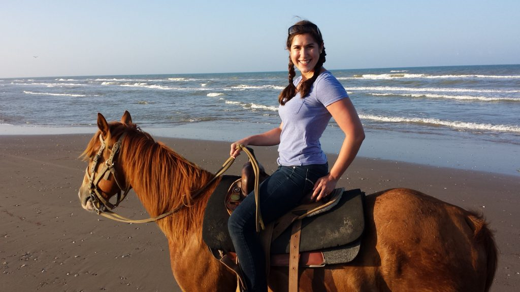 Kate Storm riding a chestnut horse on the beach in South Padre Island Texas