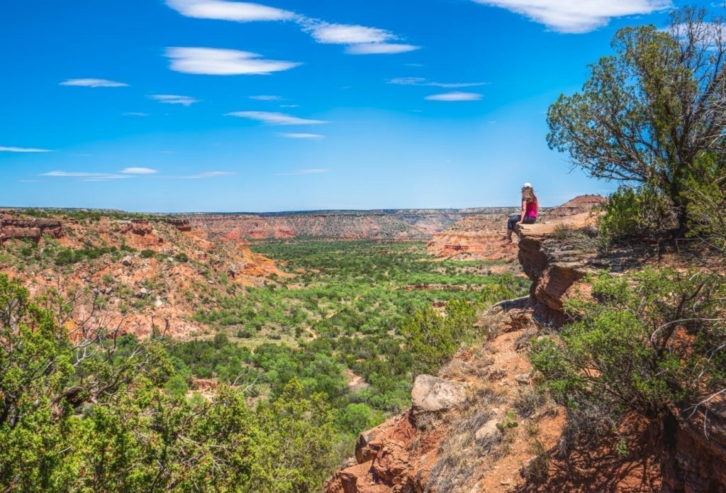 Kate Storm sitting on a ledge overlooking palo duro canyon near amarillo texas