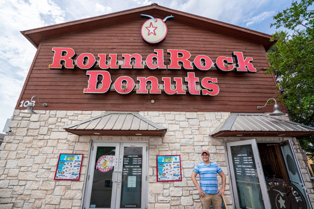 Jeremy Storm standing in front of Round Rock Donuts building, one of the best places to visit in Round Rock TX
