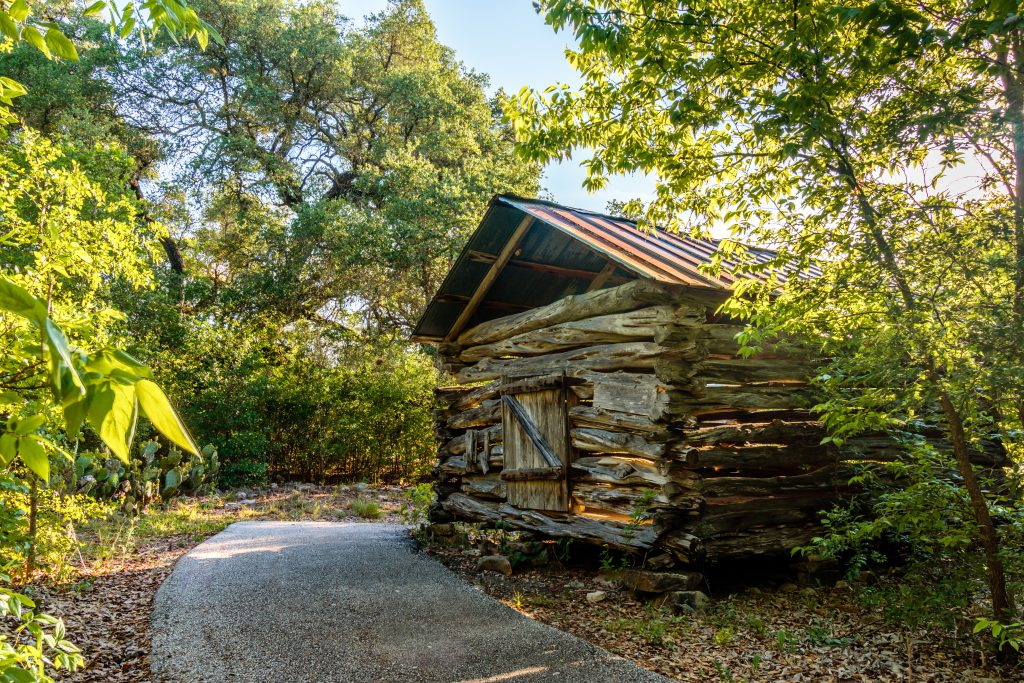 19th century cabin at Balcones Canyonlands National Wildlife Refuse, with a paved path to the left side of the photo