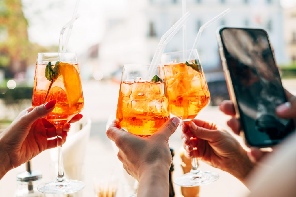 3 aperol spritzes being held up to the camera with a smartphone in the shot that is photographing the drinks