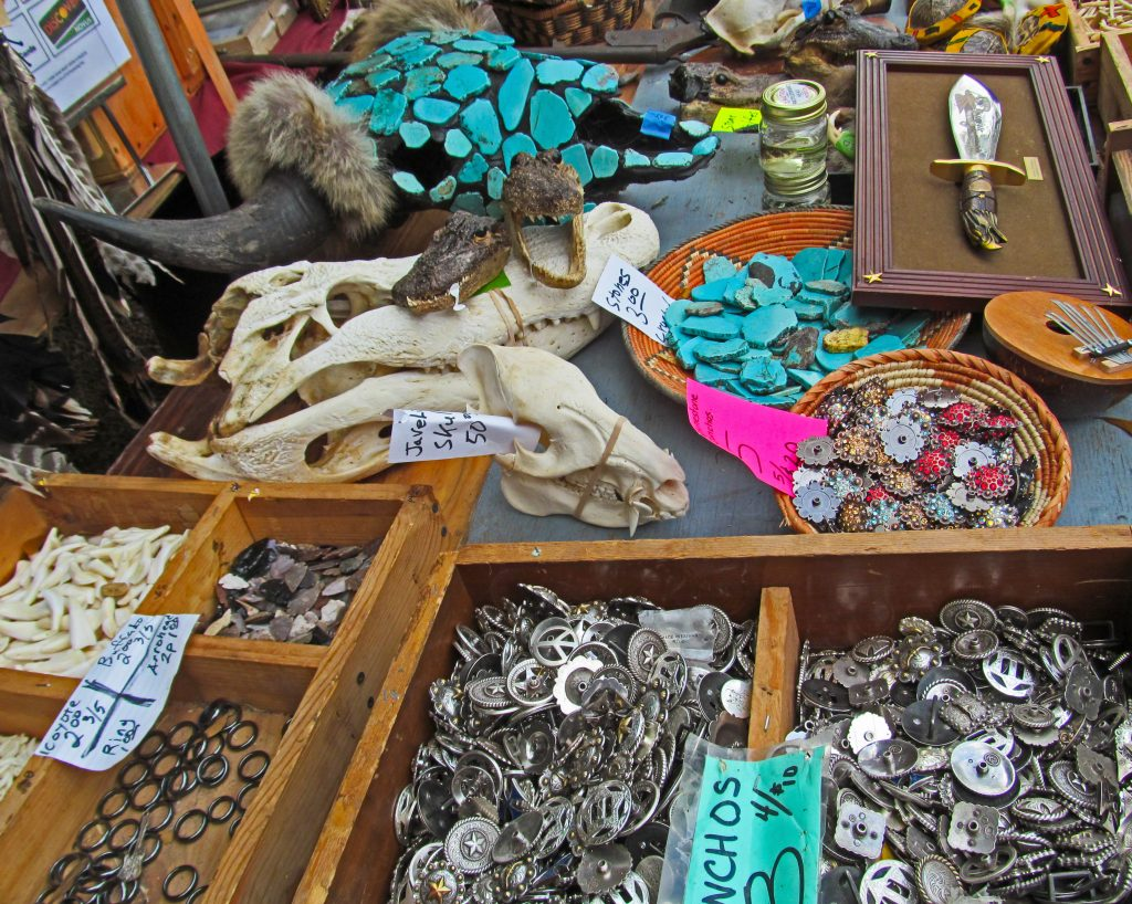Table of goods for sale at a Texas flea market with turquoise and silver jewelry visible