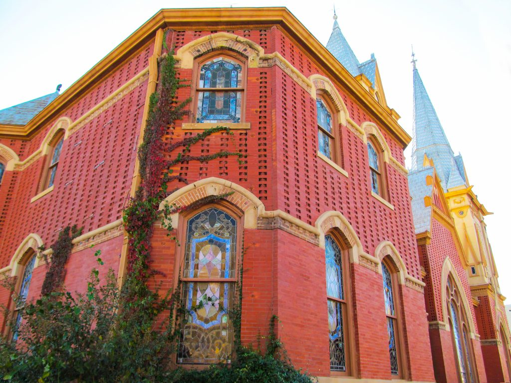 Red brick church in Greenville TX with stained glass windows