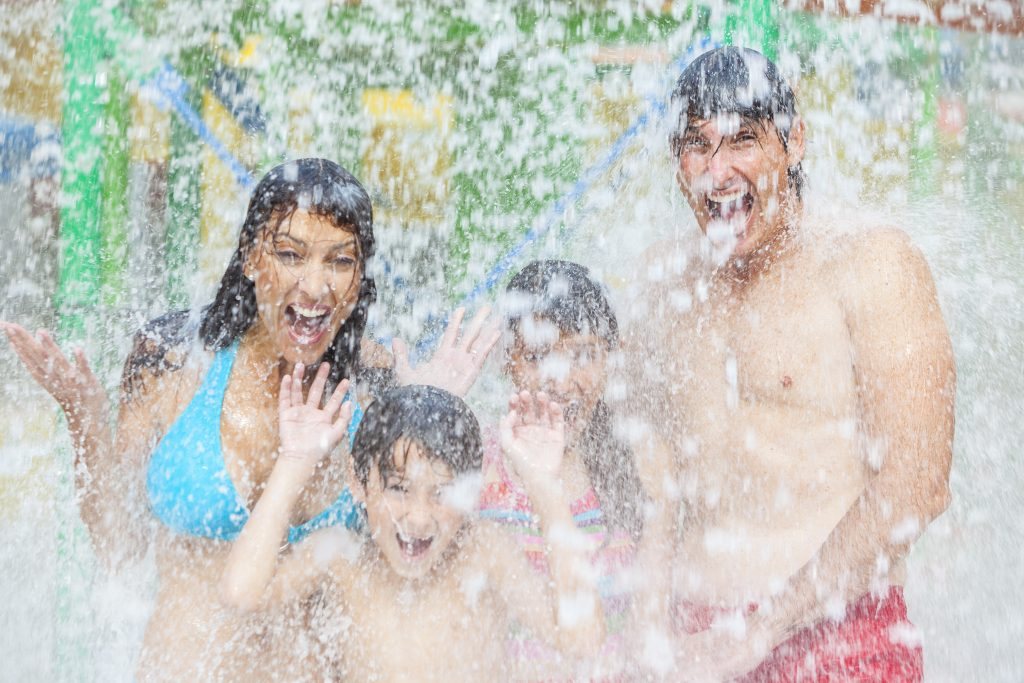 family of four being doused with water at a water park