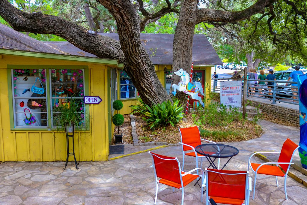 Bright yellow building in downtown Wimberley with a small table with red chairs in front of it. Wimberley is one of the most romantic getaways in Texas