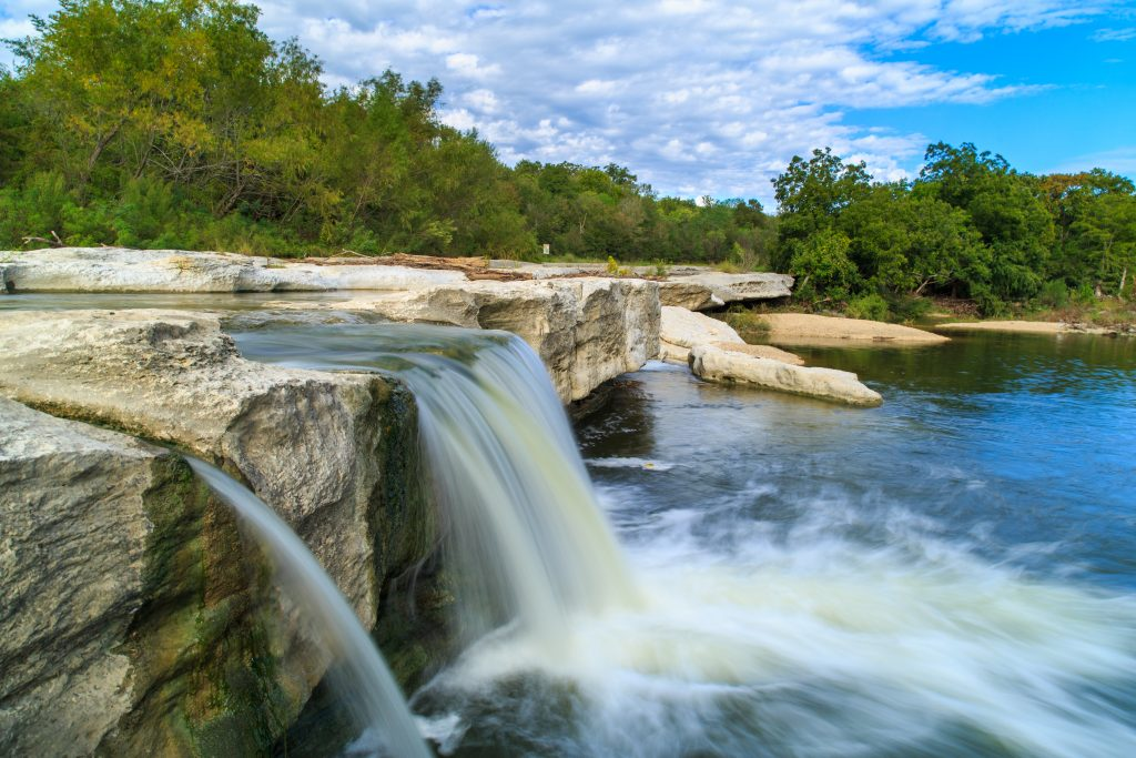 Small waterfall over limestone at MicKinney Falls State Park TX