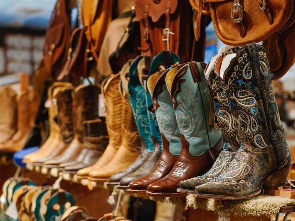 Cowboy boots lined up on a shelf with saddles about them. Cowboy boots are one of the most classic things to buy in Texas!