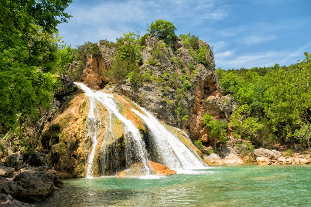 Turner Falls State Park waterfall in Oklahoma with a pool visible on the right and the waterfall on the left of the photo