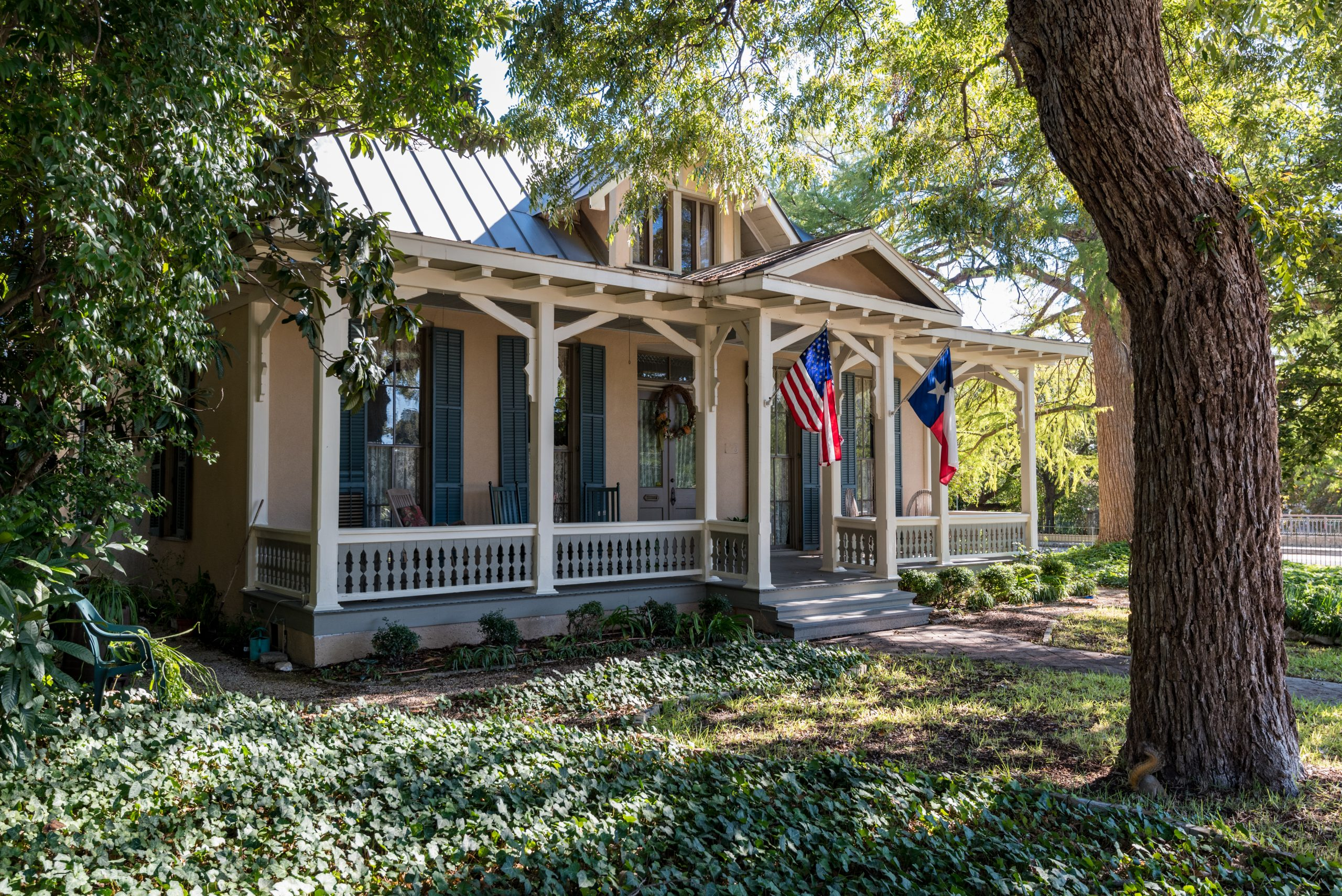 Texas house with a white front porch and black shutters shaded by a live oak tree in the King William Historic District San Antonio