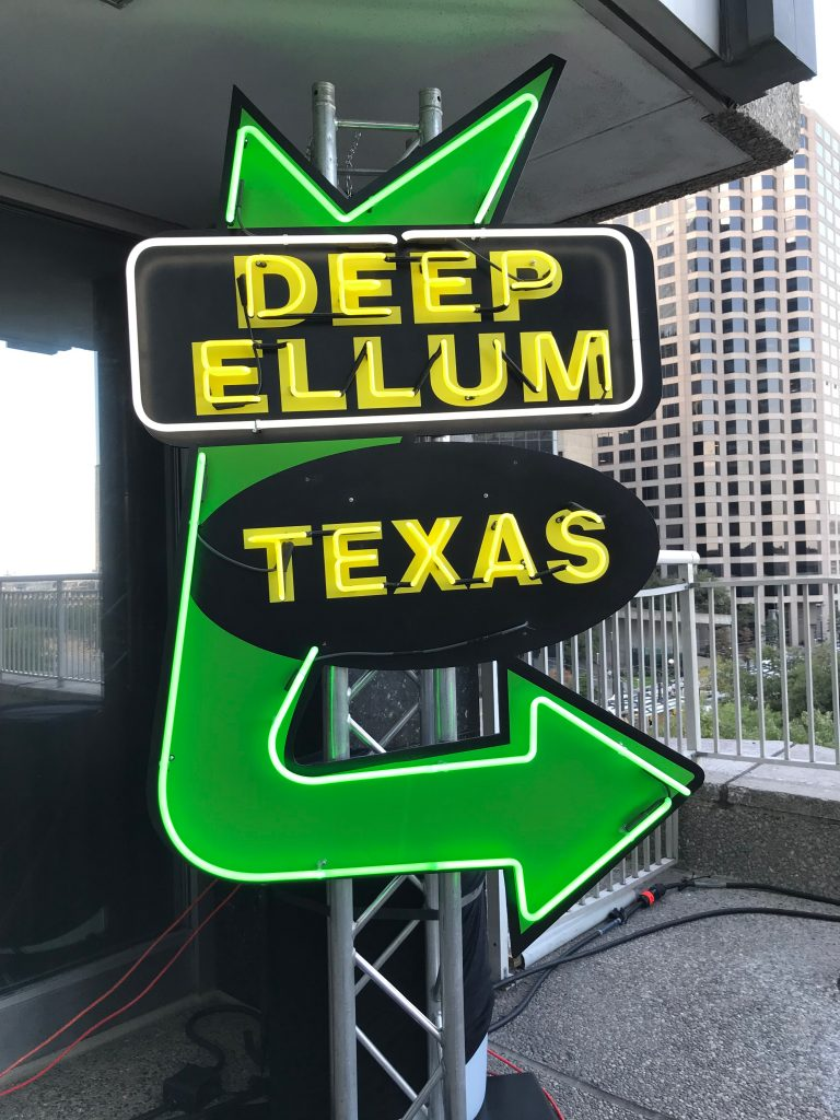 "Green and yellow neon sign that says ""deep ellum texas"""