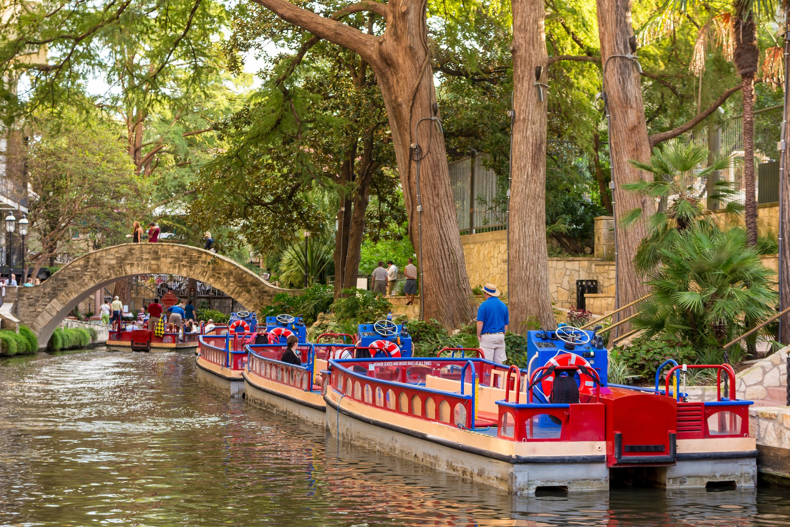 Colorful tourist boats parked along the Riverwalk in San Antonio. The Riverwalk is one of the most instagrammable places in San Antonio