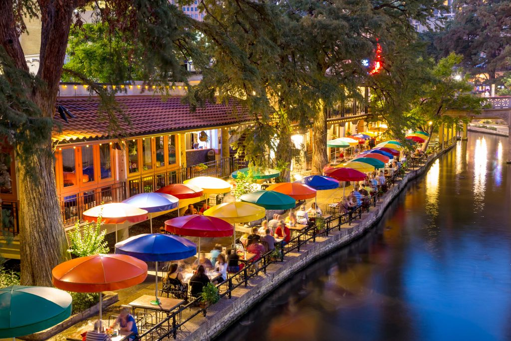 San Antonio Texas River Walk as seen from above at night with colorful umbrellas on the left side of the photo