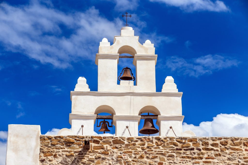 Top of Mission San Juan Capistrano church with 3 bells set in white stucco. The San Antonio Missions are some of the most instagrammable places in san antonio texas