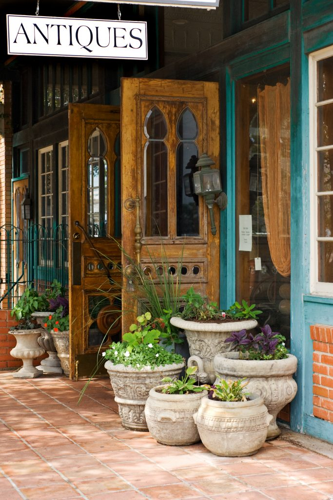 Wooden door opening to an antique store in Fredericksburg Texas. Antiques are some of the best souvenirs from Texas