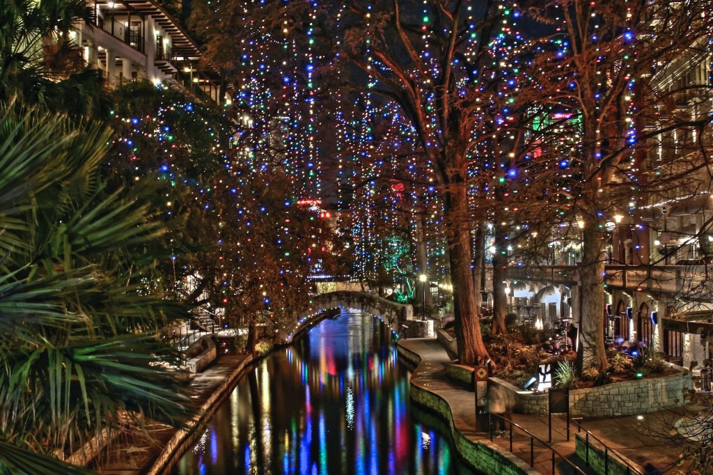 Riverwalk of San Antonio photographed at night with holiday light display dangling from the trees
