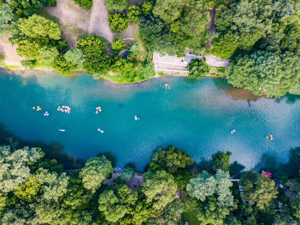 View of Guadalupe River from above with Texans floating on it. Guadalupe River State Park is one of the best day trips from San Antonio TX