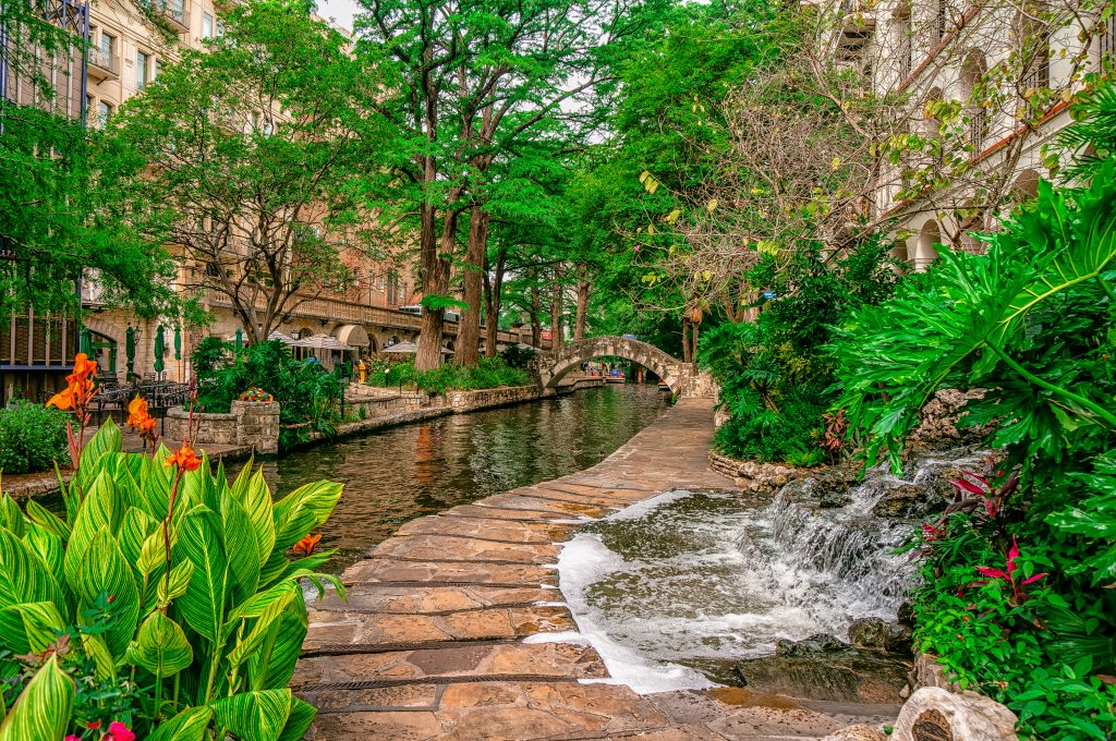 Cobblestone path on the San Antonio Riverwalk with a small waterfall visible to the right