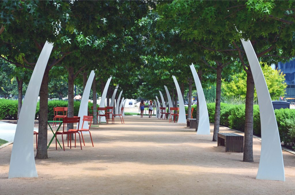 Series of white statues lining a tree-shaded pathway at Klyde Warren Park in Dallas Texas