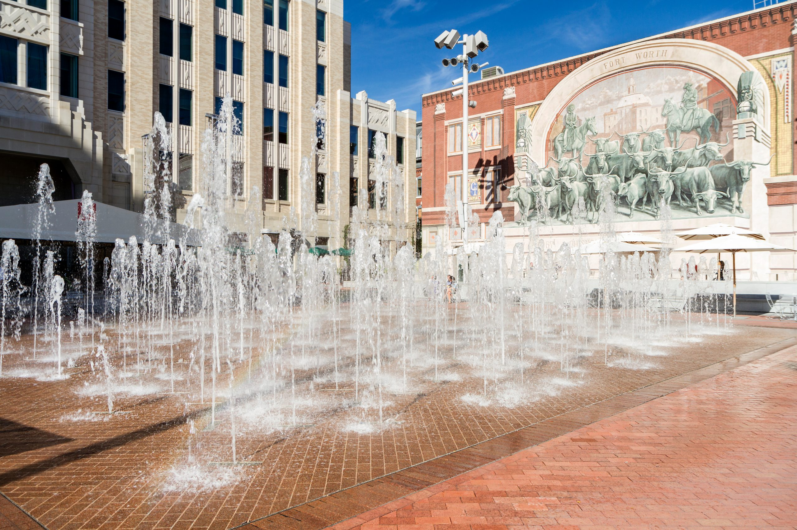 Sundance Square in Ft Worth TX with the fountains on during a sunny day, visiting sundance square is one of the fun things to do in fort worth texas
