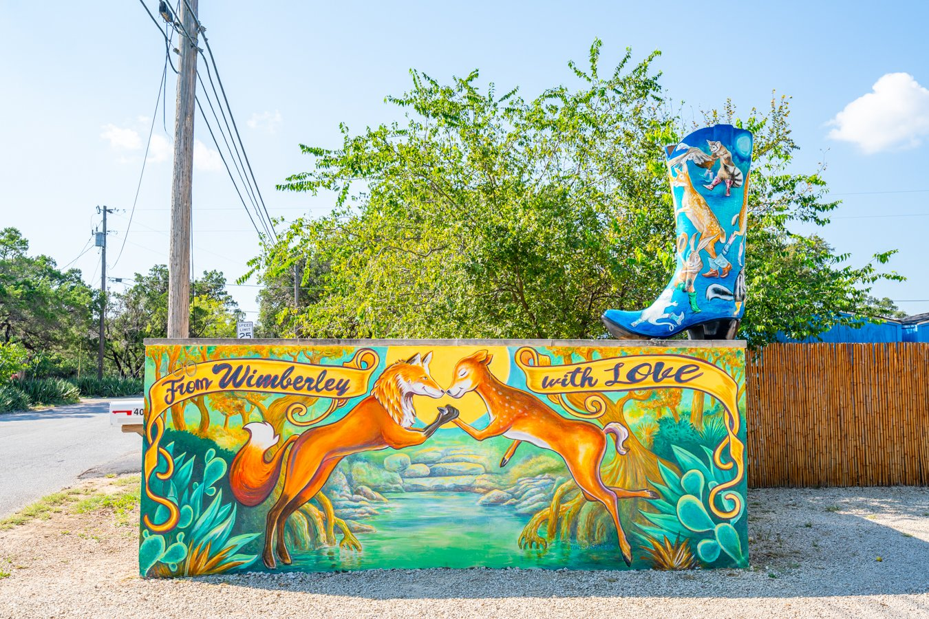 mural of two colorful foxes in wimberley texas with a painted boot on top--tracking down the painted boots is one of the fun things to do in wimberley tx