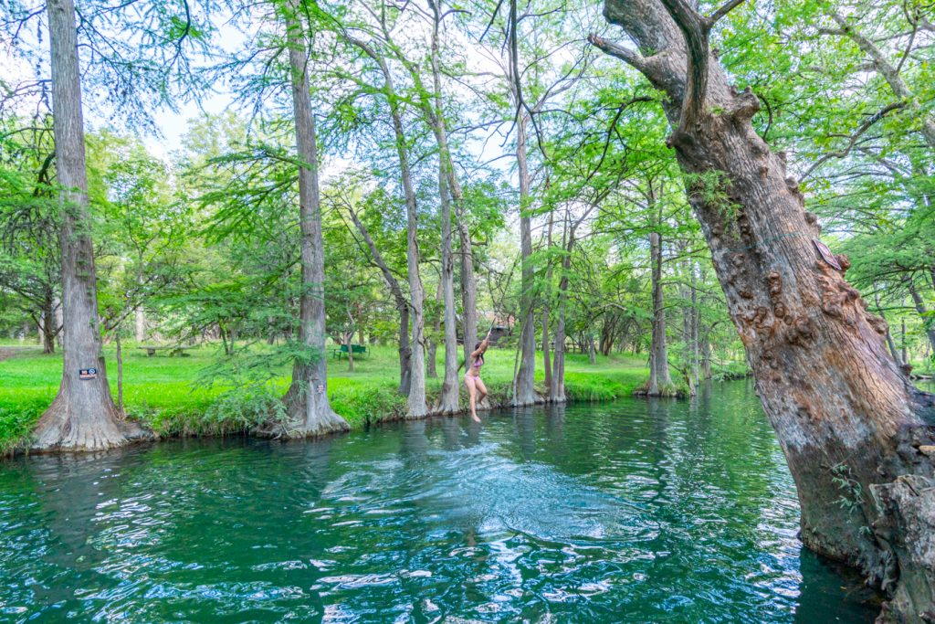 Kate Storm swinging from a metal ring above the water at the Wimberley Blue Hole