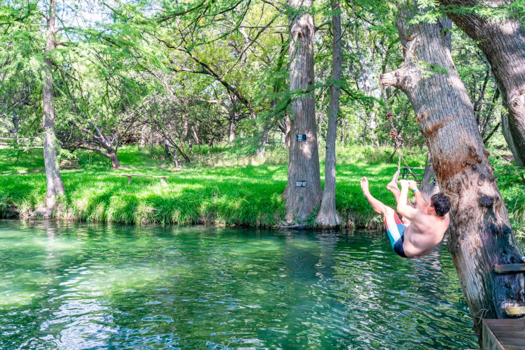 Jeremy Storm swinging into the Blue Hole in Wimberley Texas while holding a metal ring