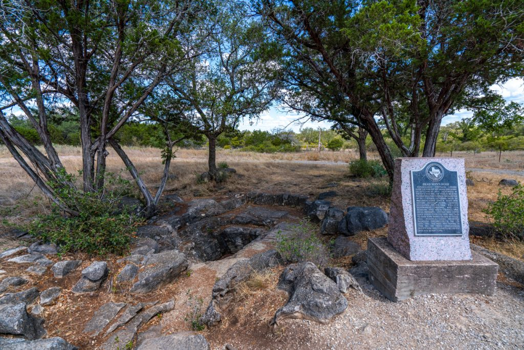 Plaque sharing history of Dead Man's Hole in Marble Falls with the entrance to the hole visible behind it