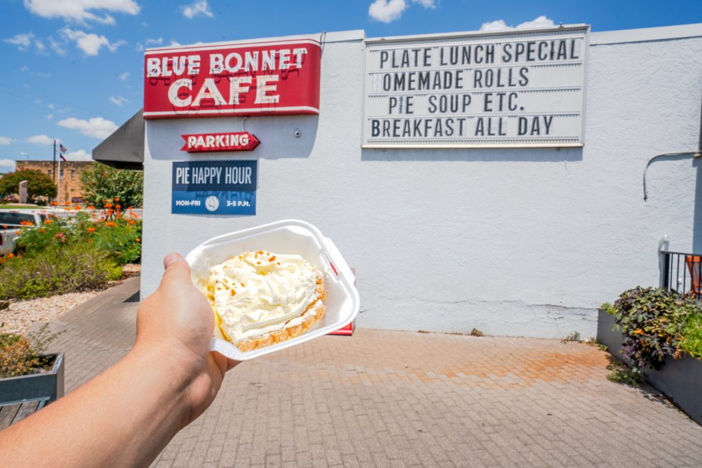jeremy storm holding a slice of pie in front of the blue bonnet cafe marble falls texas