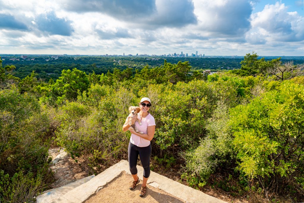 Kate Storm in a pink shirt and sunglasses holding a puppy up to the camera at Mount Bonnell Austin TX with the downtown skyline visible in the background