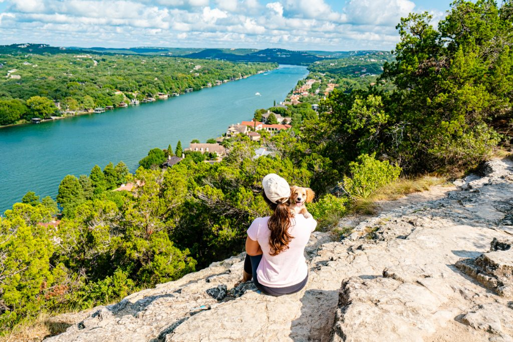 Kate Storm holding puppy Ranger over her shoulder, sitting in front of Mount Bonnell in Austin Texas