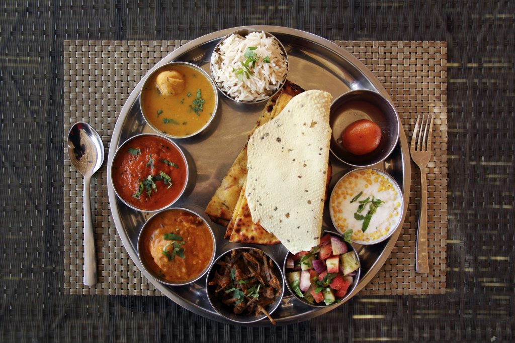 a Thali meal on a round steel tray set on a brown placement. Indian food can be a fun way to experience houston in 24 hours