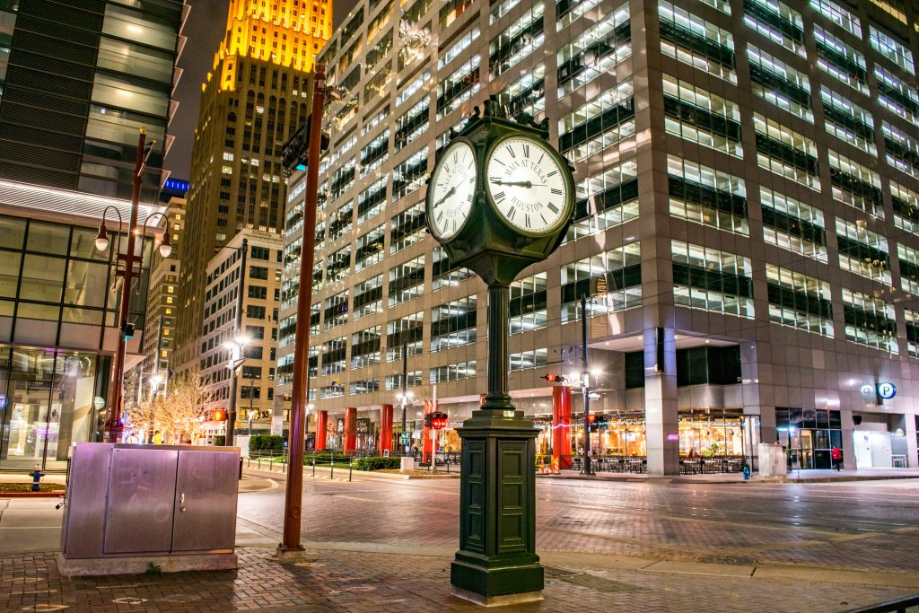 Downtown street in Houston TX at night with skyscrapers lining it and a clock in the foreground
