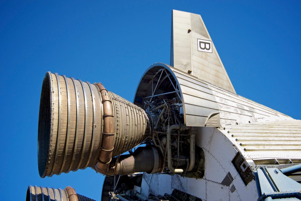 Rear end of a parked rocket ship set against a bright blue sky