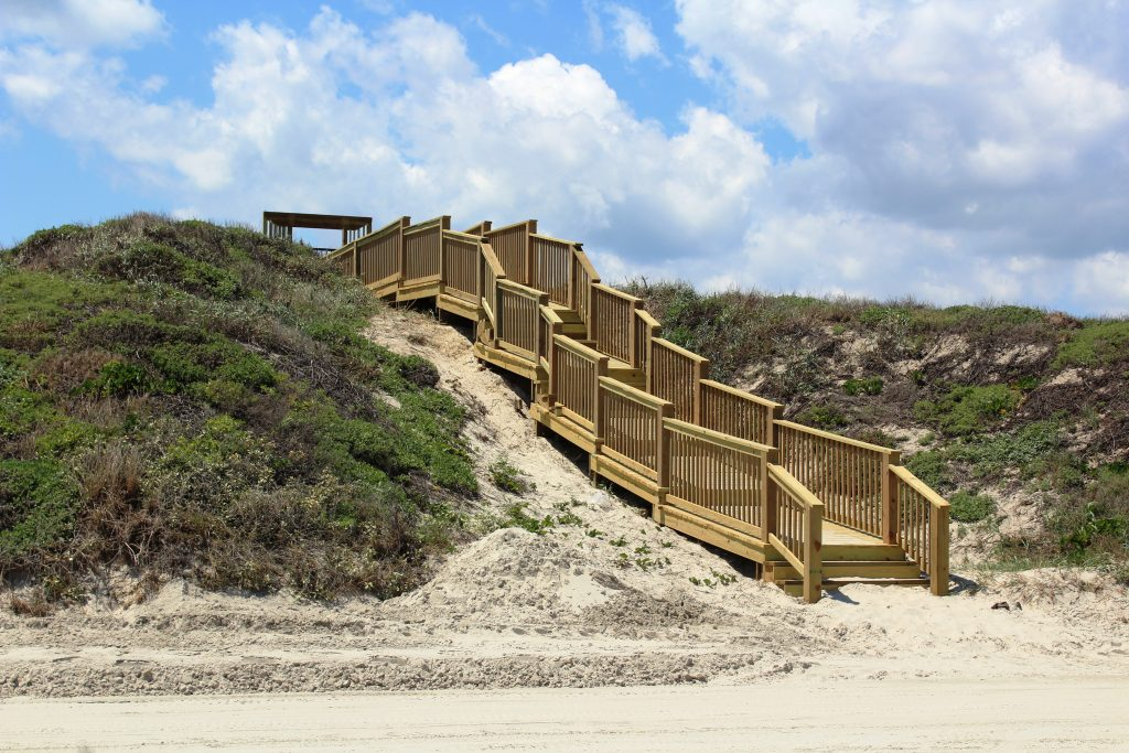 Wood stairs leading down to a sandy beach in Port Aransas Texas
