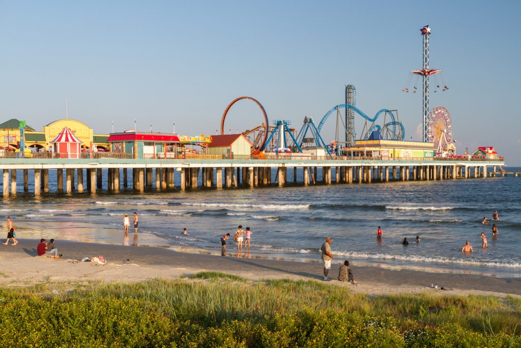 Galveston Pier with beach in the foreground where people are swimming. Galveston is one of the best houston day trips