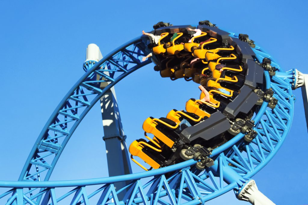 Blue iron roller coaster loop as seen looking up with a yellow train car on it