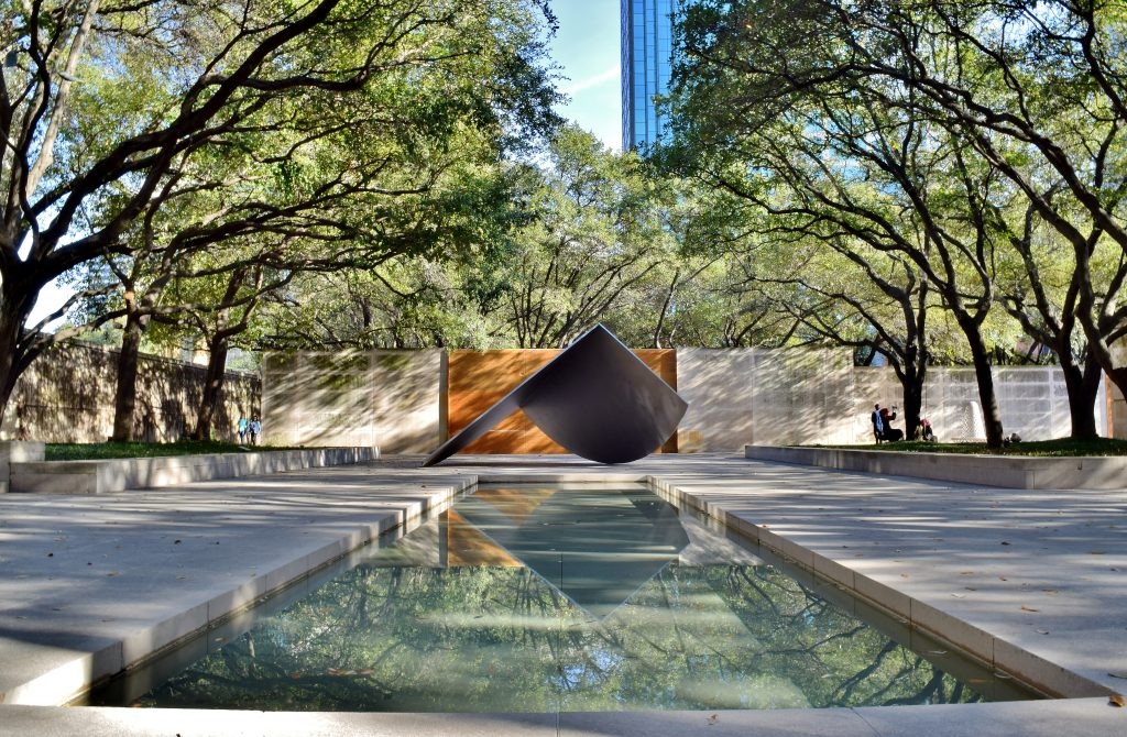 Reflecting pool in downtown Dallas lined with oak trees. You'll see plenty of pretty spots like this when enjoying a long weekend in Dallas tx
