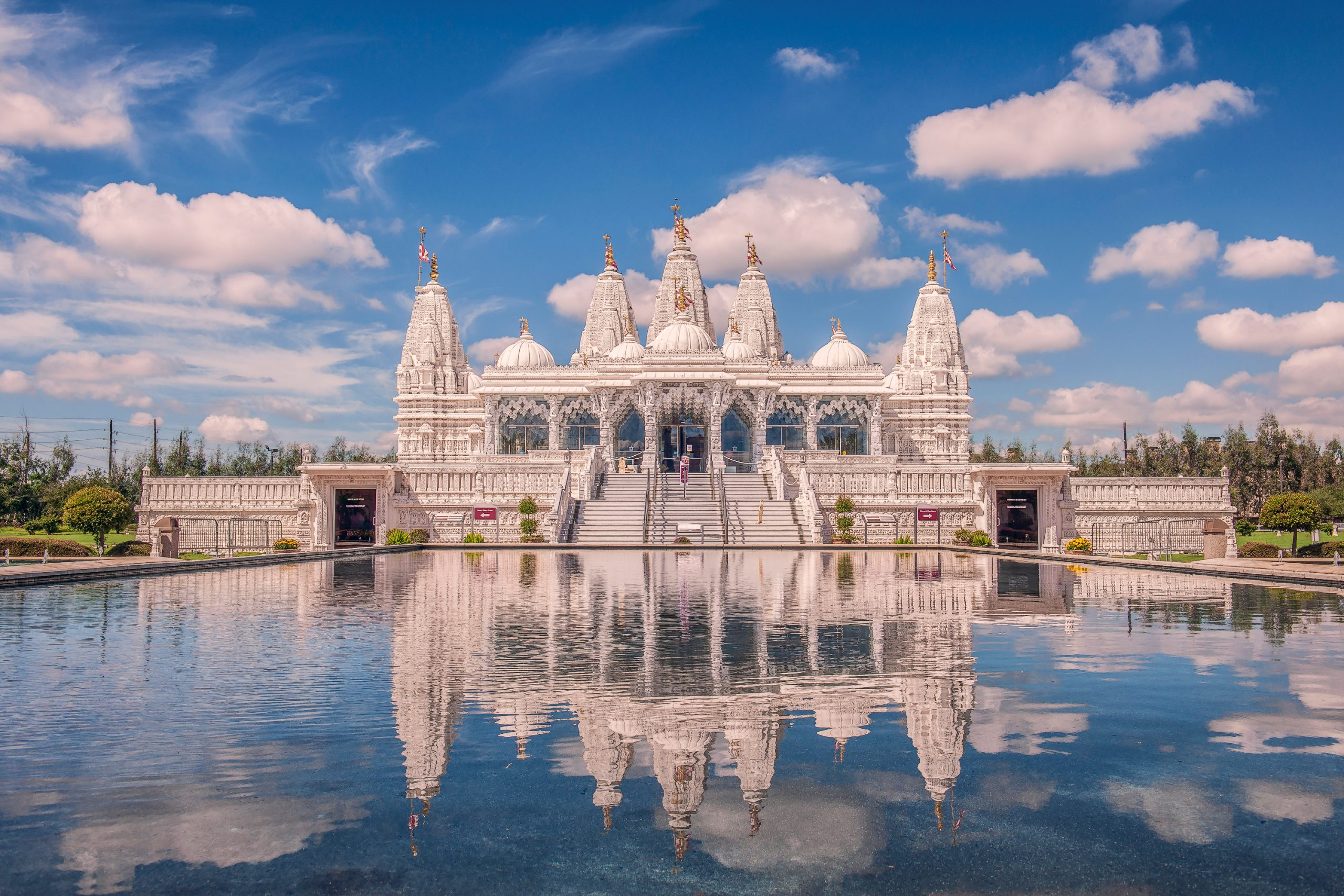 BAPS Shri Swaminarayan Temple as seen across a reflection pool. This traditional Hindu temple is one of the best places to take pictures in Houston TX