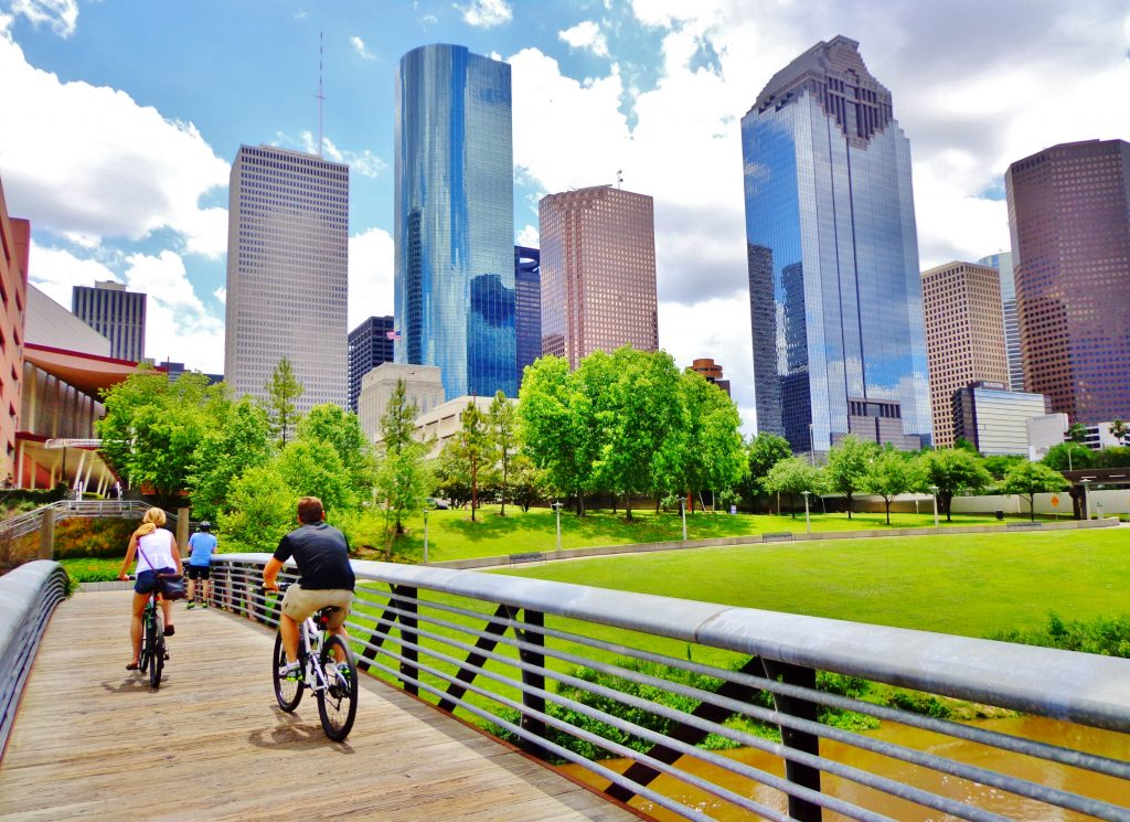 Two cyclists crossing a bridge in Buffalo Bayou Park Houston with the downtown skyline in the background