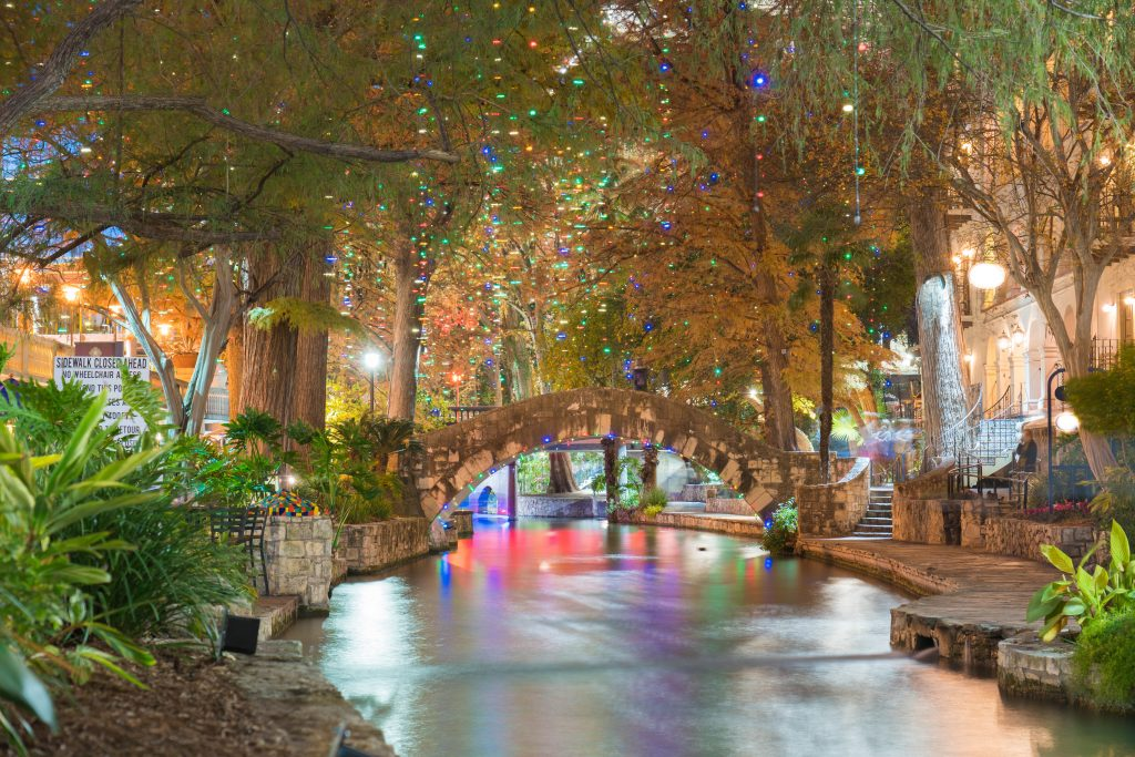 San Antonio Riverwalk with a bridge in the center of the shot and Christmas lights hanging from trees