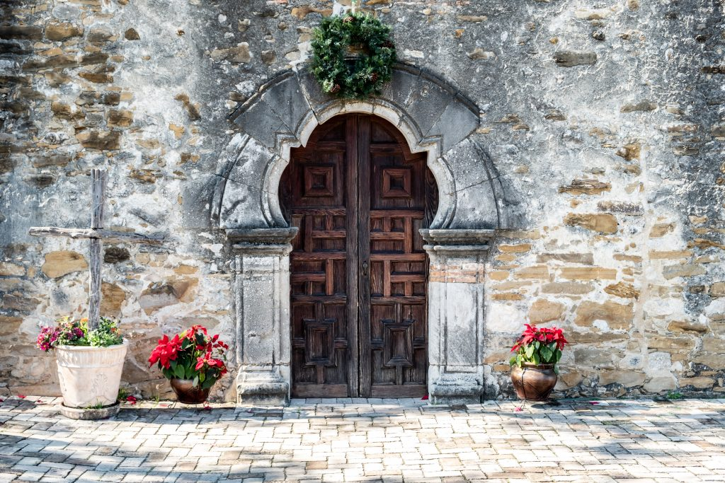 Front door of Mission Espada in San Antonio with Christmas decorations in front