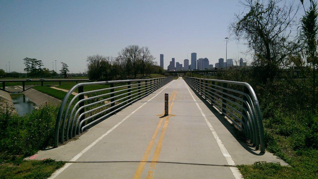 Bridge near White Oak Bayou with biking lanes and the Houston skyline in the background