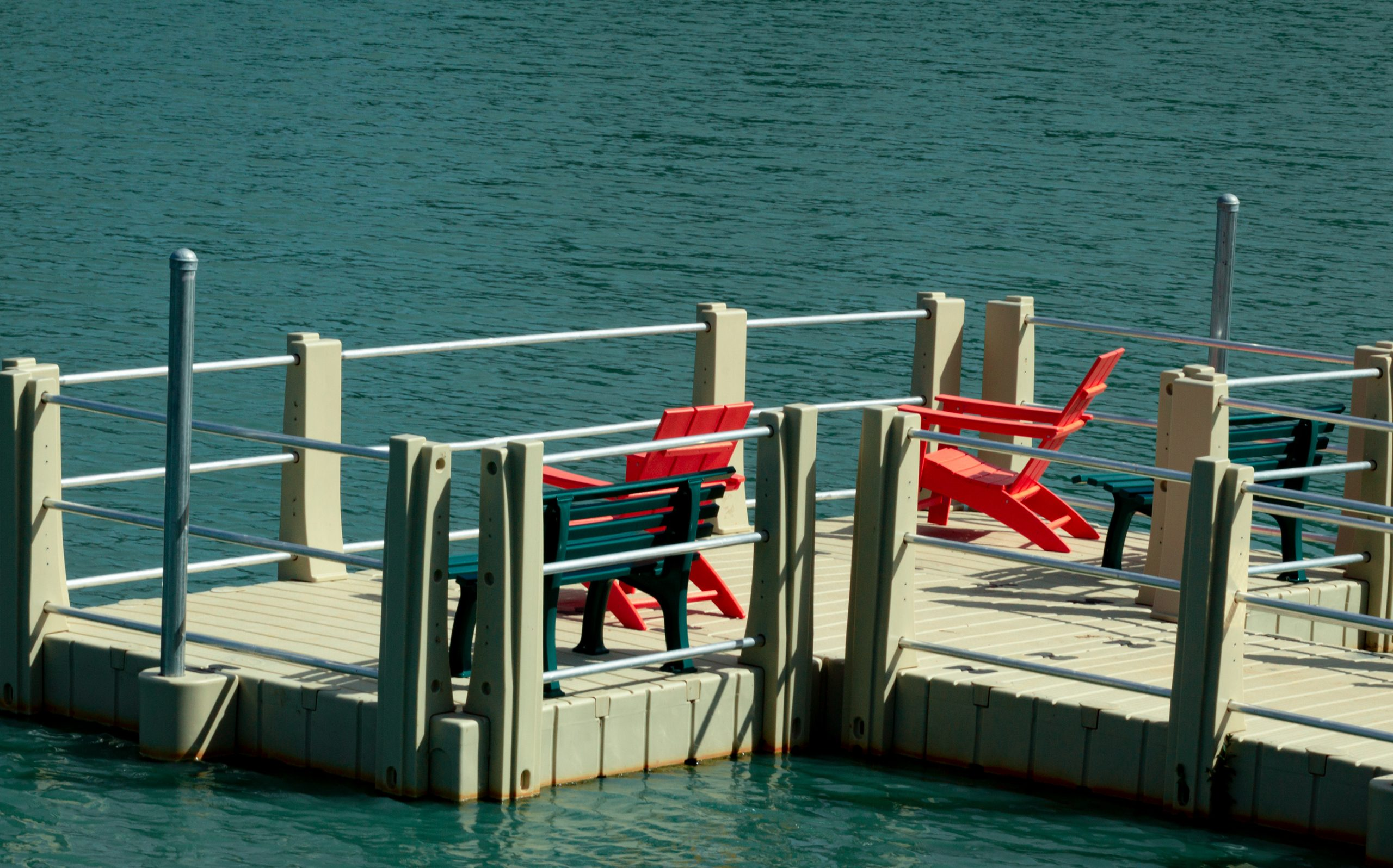 2 red chairs on a dock overlooking the lake in Conroe--many of the best things to do in Conroe tx revolve around the lake!