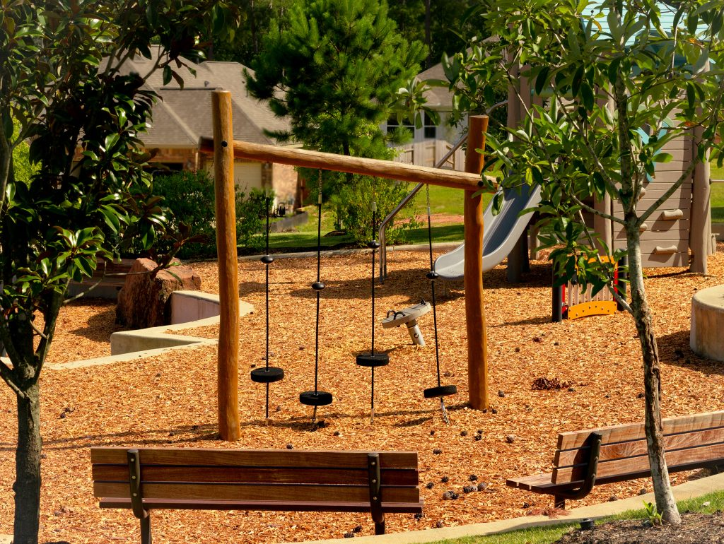 Playground at a small park in Conroe Texas with benches in the foreground and a swing set in the background
